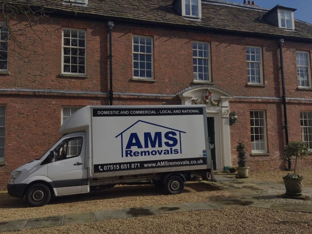AMS Removals van parked in front of big movers Manchester house