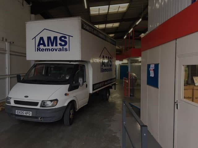 AMS Removals van parked in storage warehouse