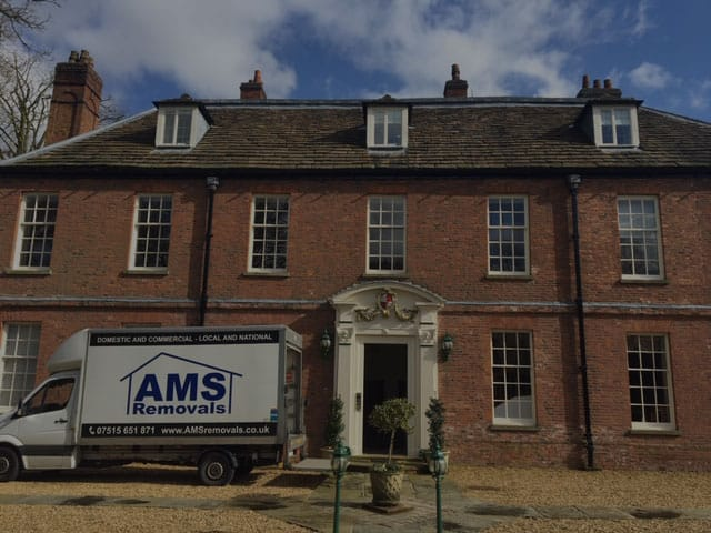 AMS Removals van parked in front of big movers Manchester house second image